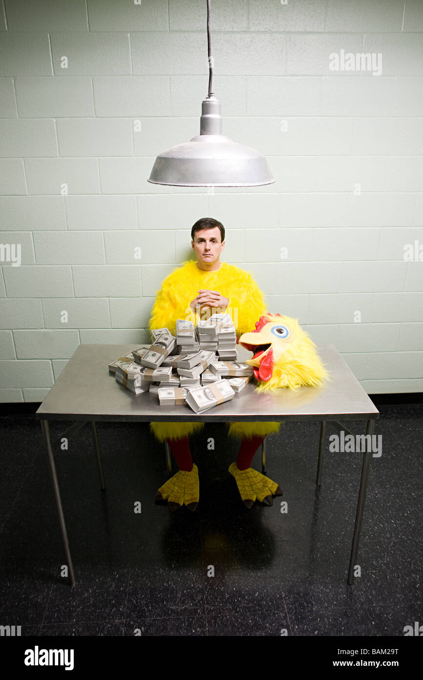 Criminal in chicken suit with money - Stock Image