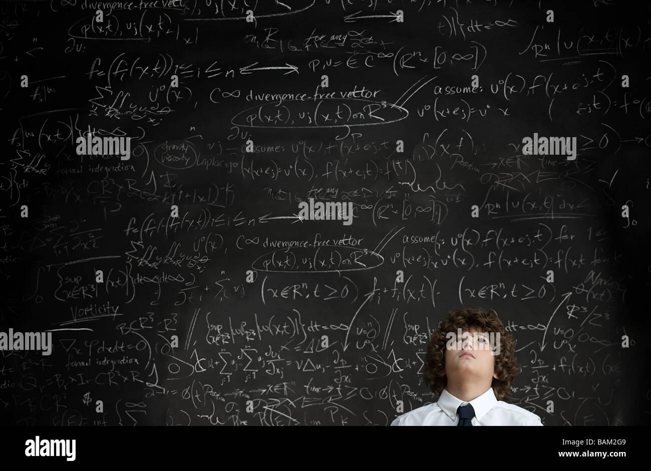 Boy in front of blackboard - Stock Image