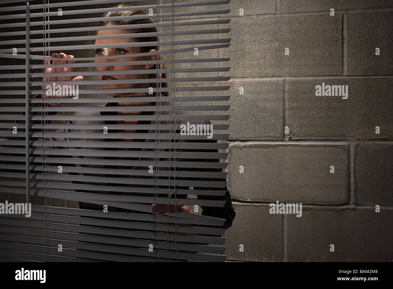 Woman looking through blinds - Stock Image