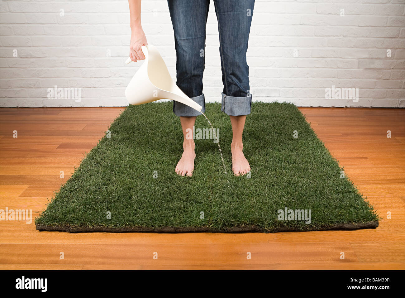 A woman watering grass - Stock Image