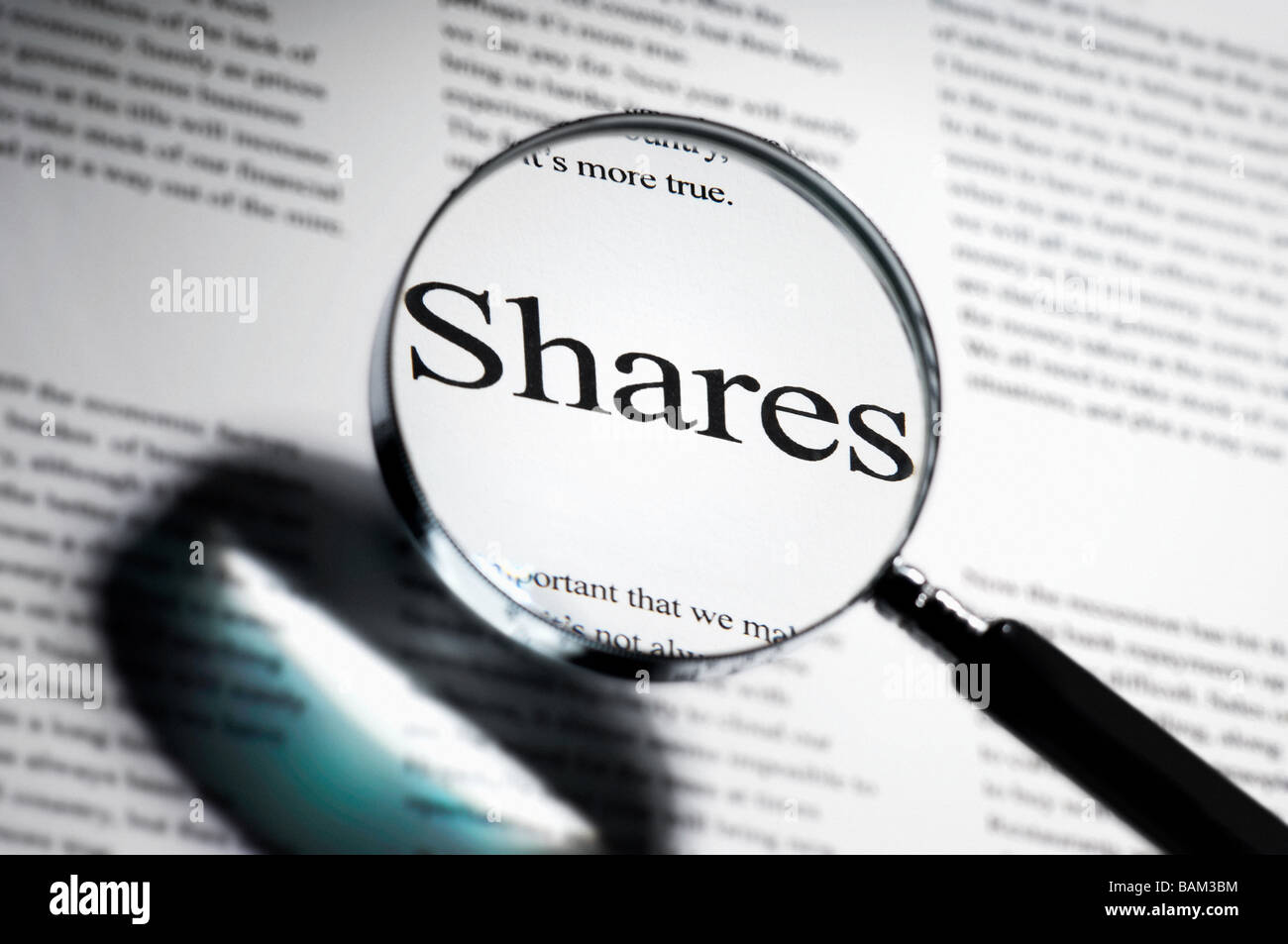 Word shares under magnifying glass - Stock Image