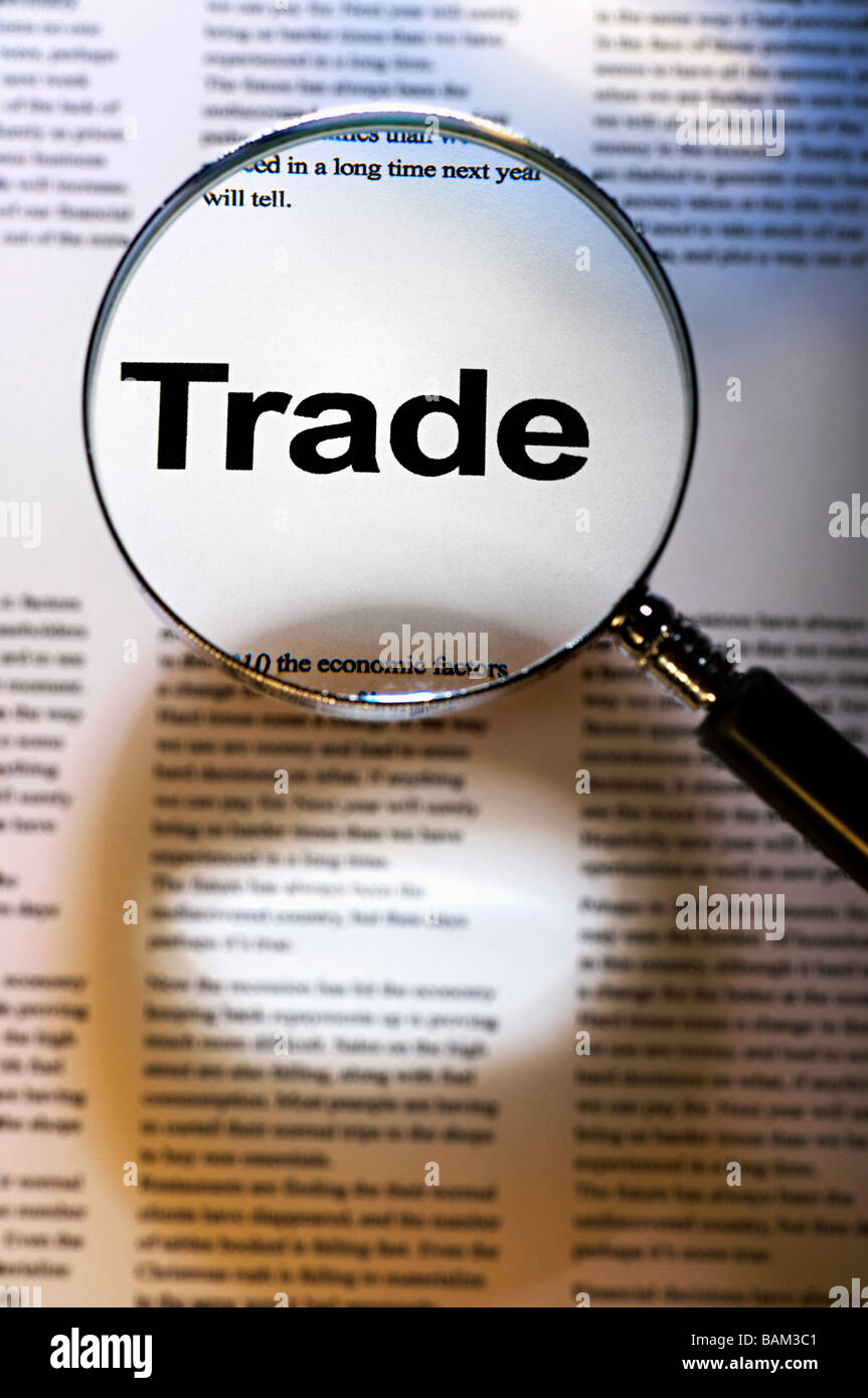 Word trade under magnifying glass - Stock Image
