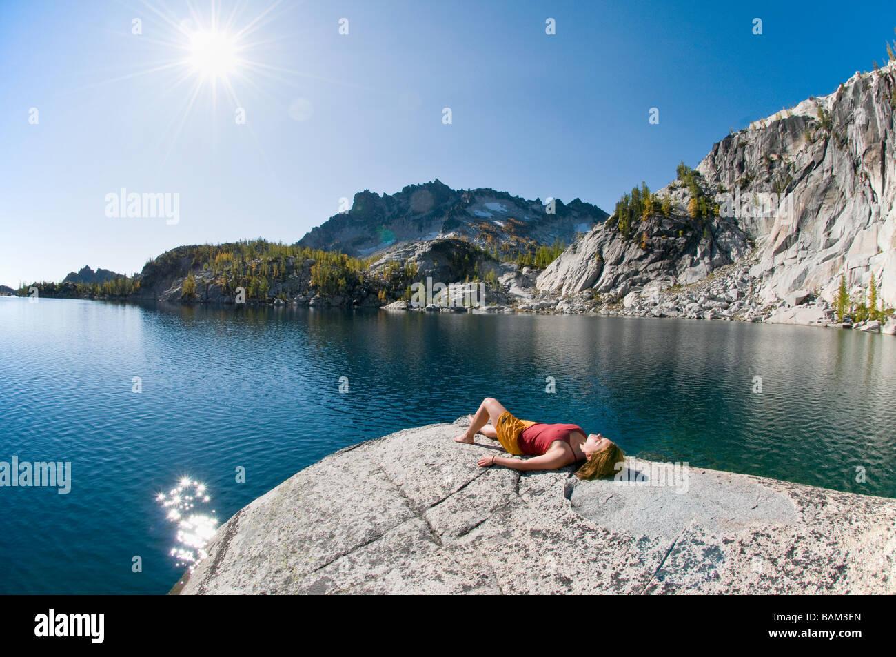 A woman sunbathing next to enchantment lakes - Stock Image
