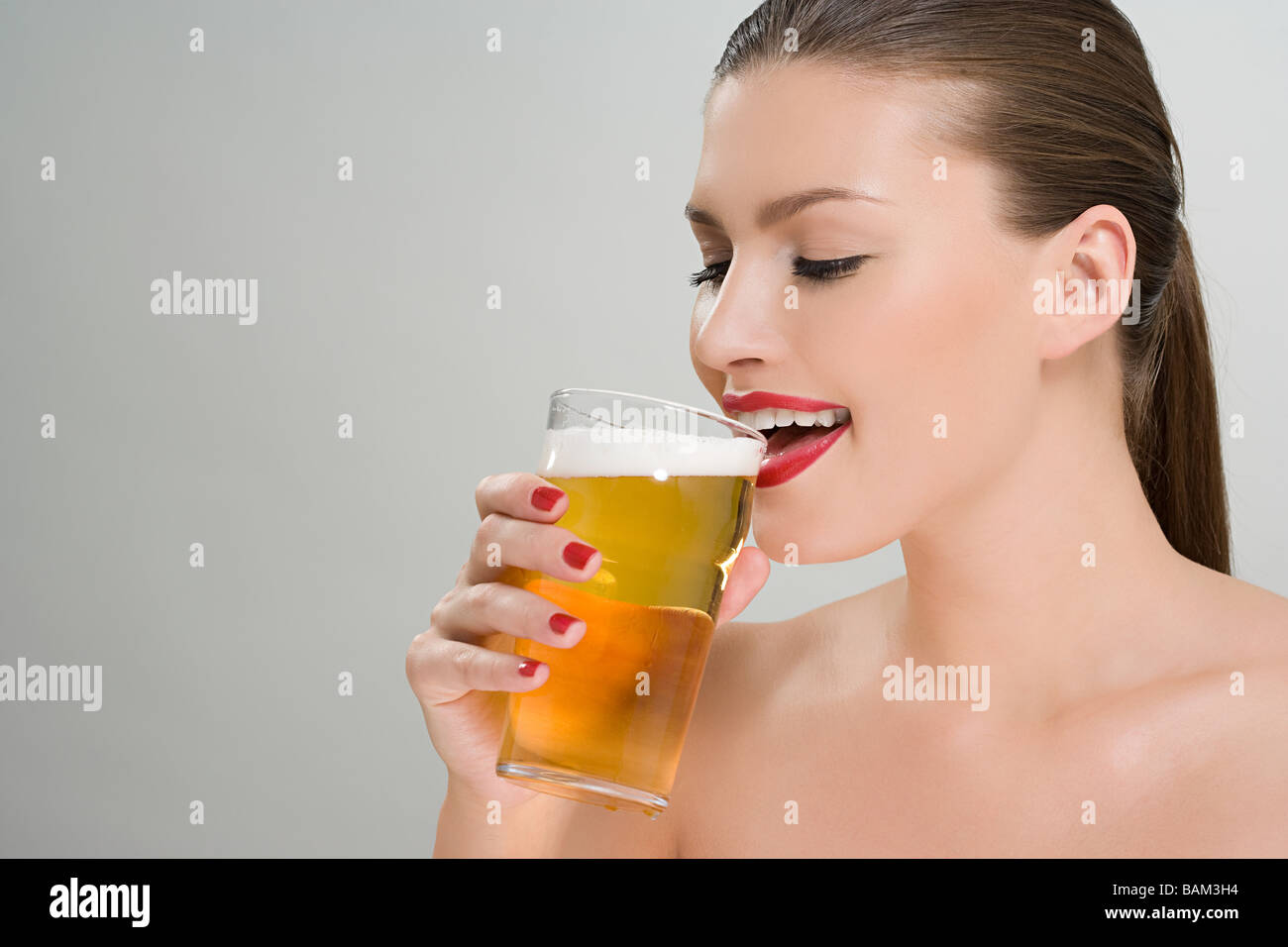 Woman drinking a pint of lager - Stock Image