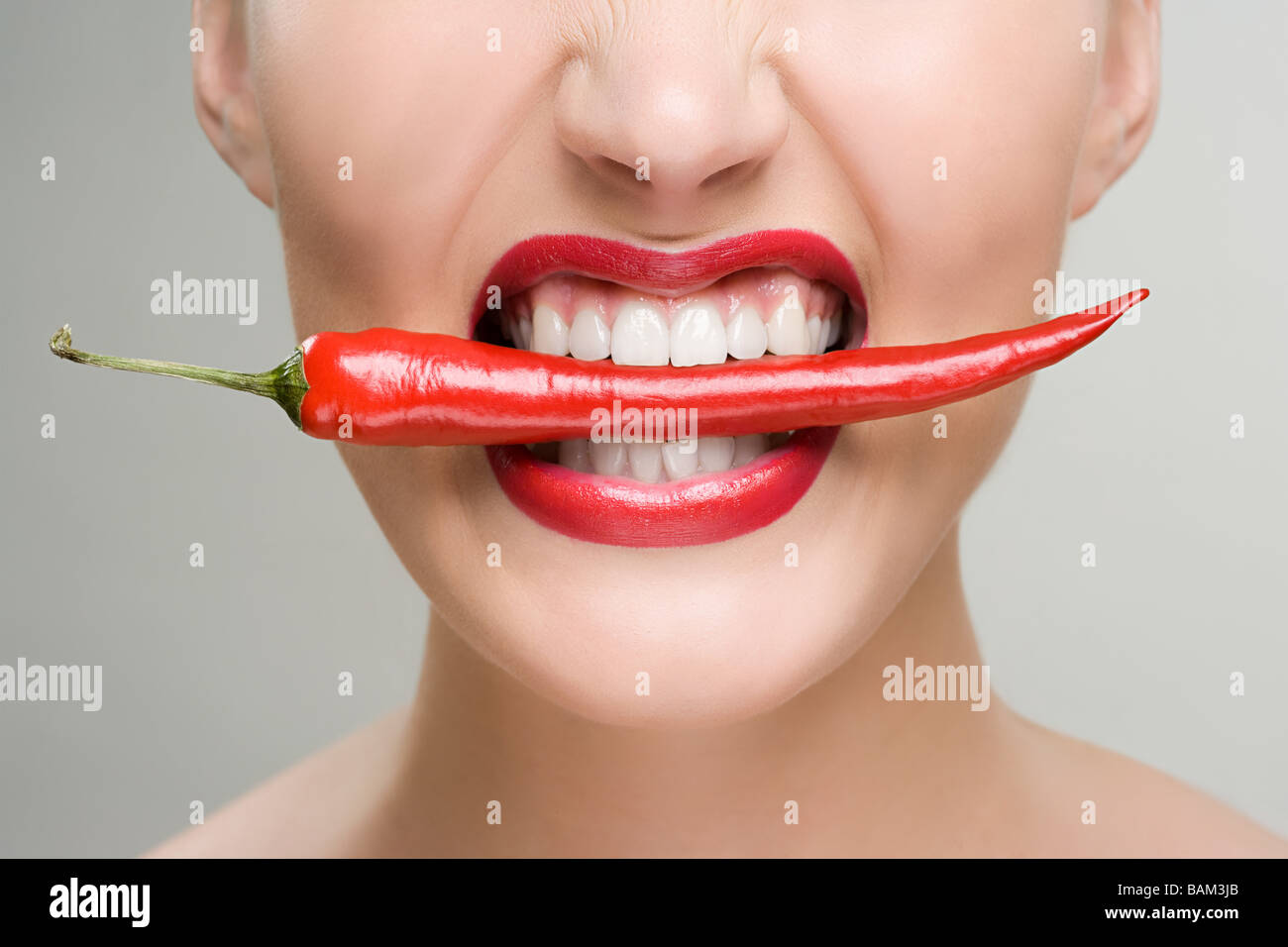 Woman with a red chili pepper between her teeth - Stock Image