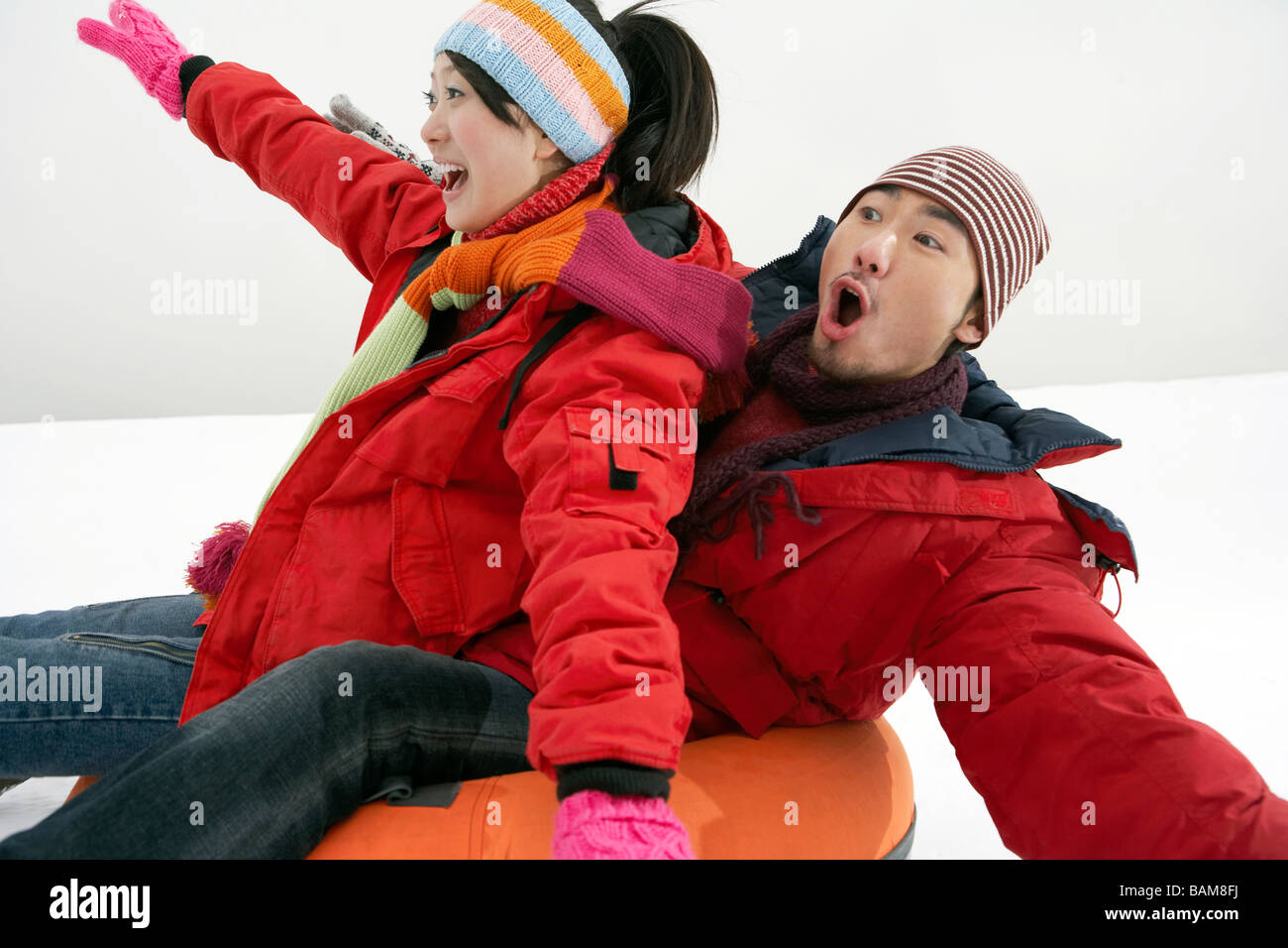 Couple Riding On Inflatable Snow Tube Stock Photo