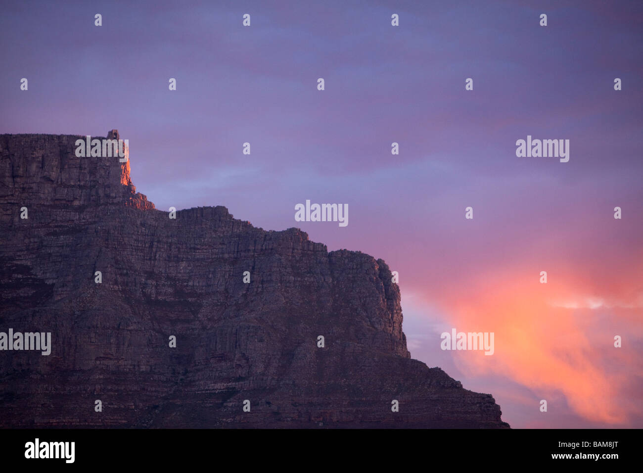 The sun lights up a wispy cloud at sunset over Table Mountain - Stock Image