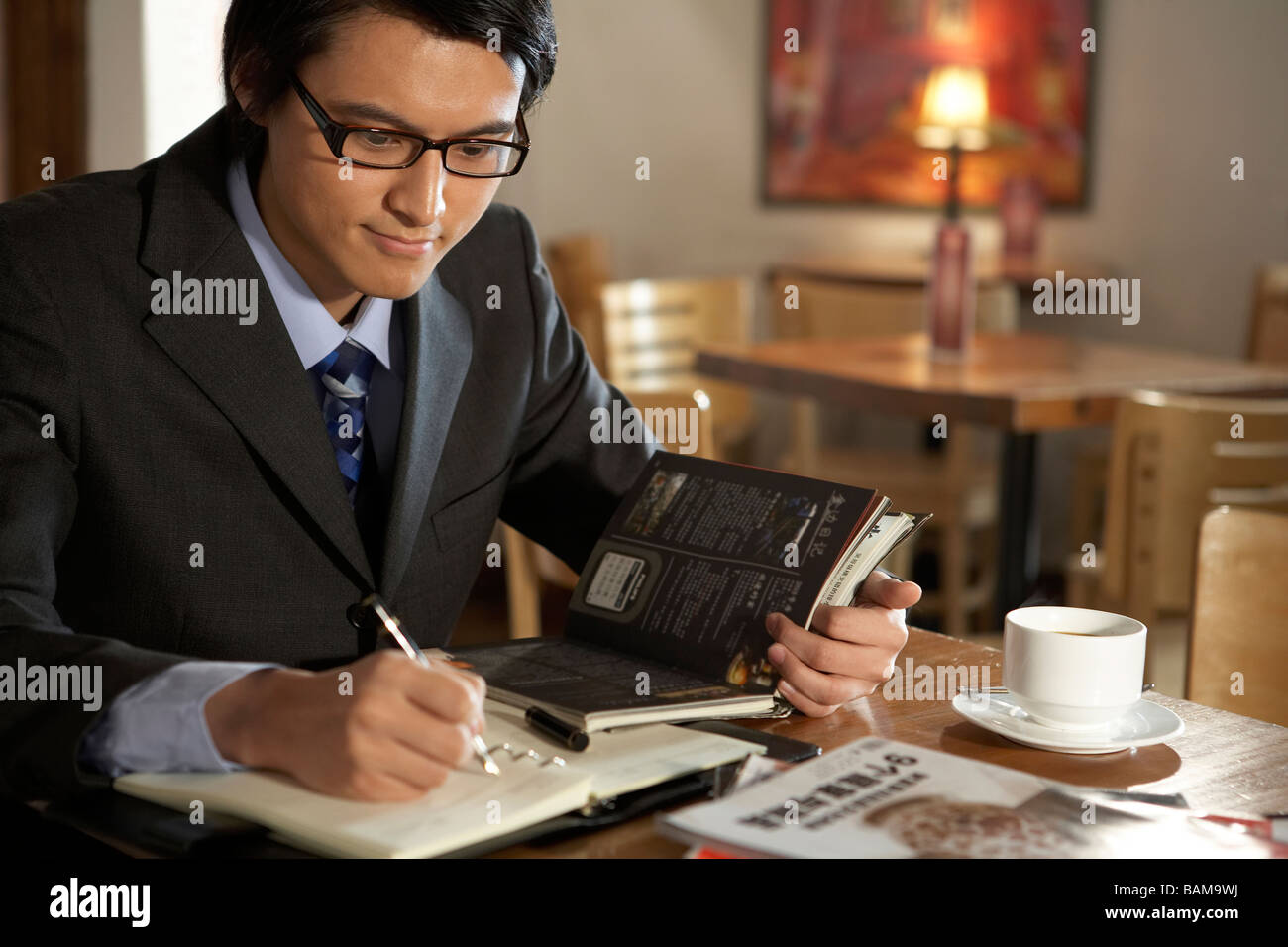Businessman Writing In A Book Stock Photo