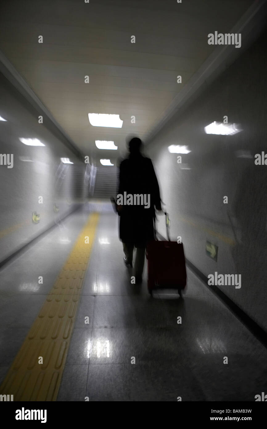 Blurred Image Of A Person Pulling A Suitcase In A Subway Terminal Stock Photo