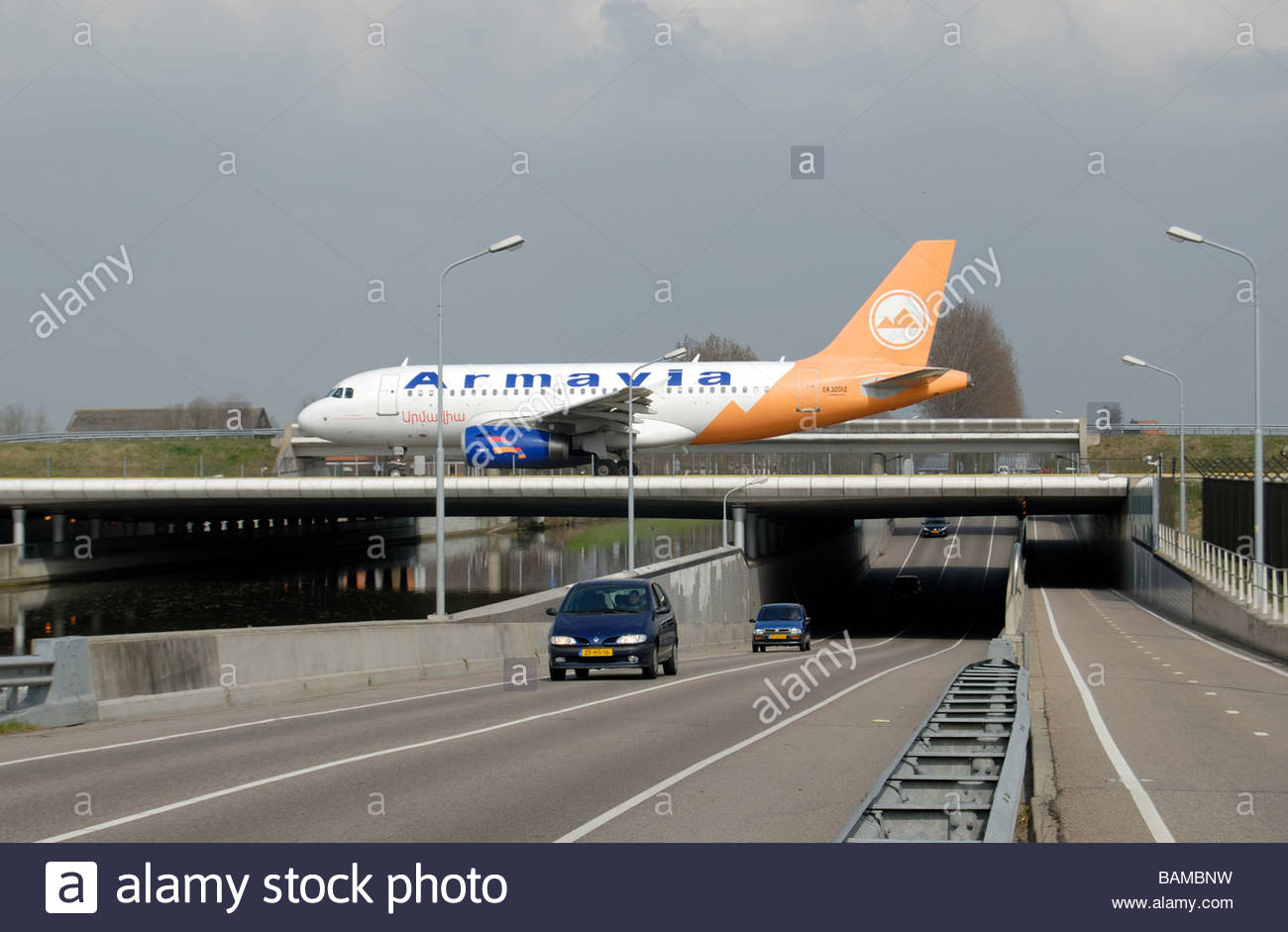 Schiphol The Netherlands An Armavia Armenian Airlines Airbus A319 taxi's across a provincial road - Stock Image