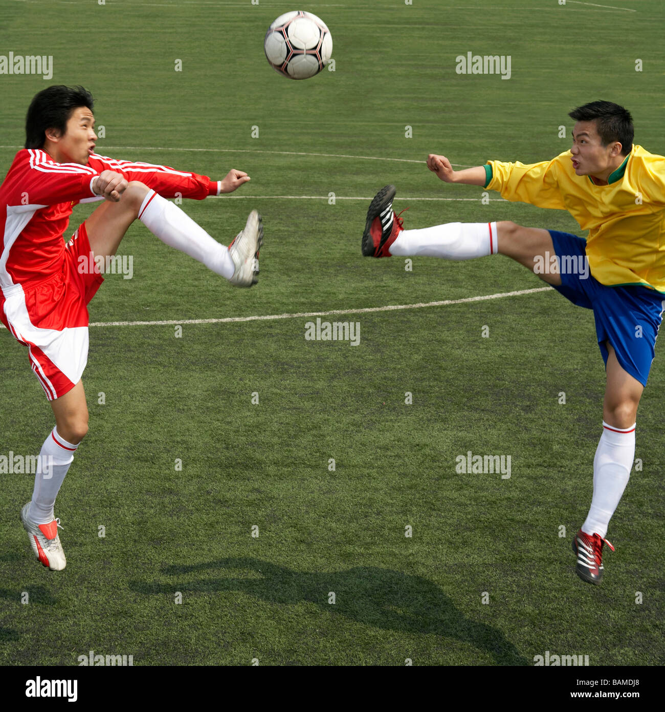Two Soccer Players Jumping For The Ball - Stock Image