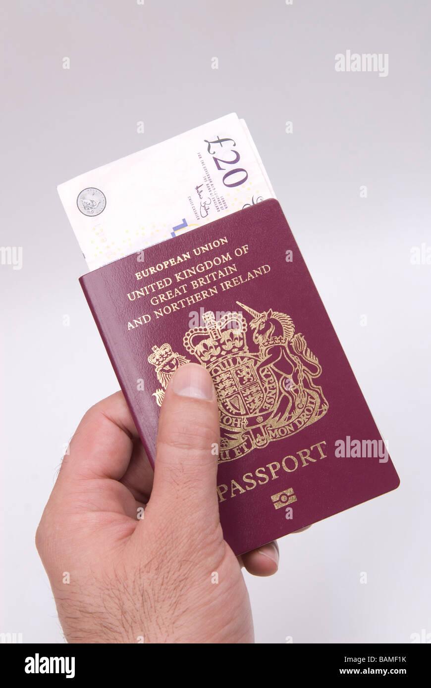 Man's hand holding a British passport and money - Stock Image