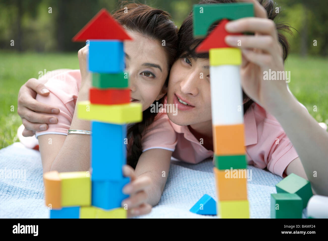 Young Couple Laying In The Park On A Blanket With Building Blocks Stock Photo