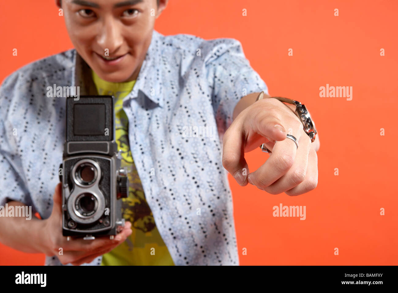 Young Man Holding Vintage Film Camera And Pointing - Stock Image