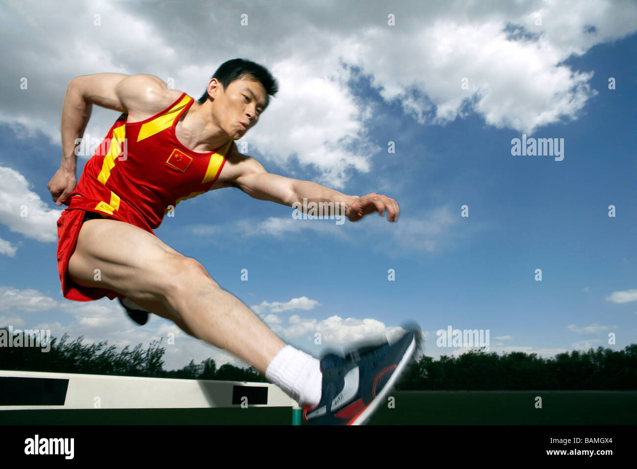 Athlete Jumping Over A Hurdle - Stock Image