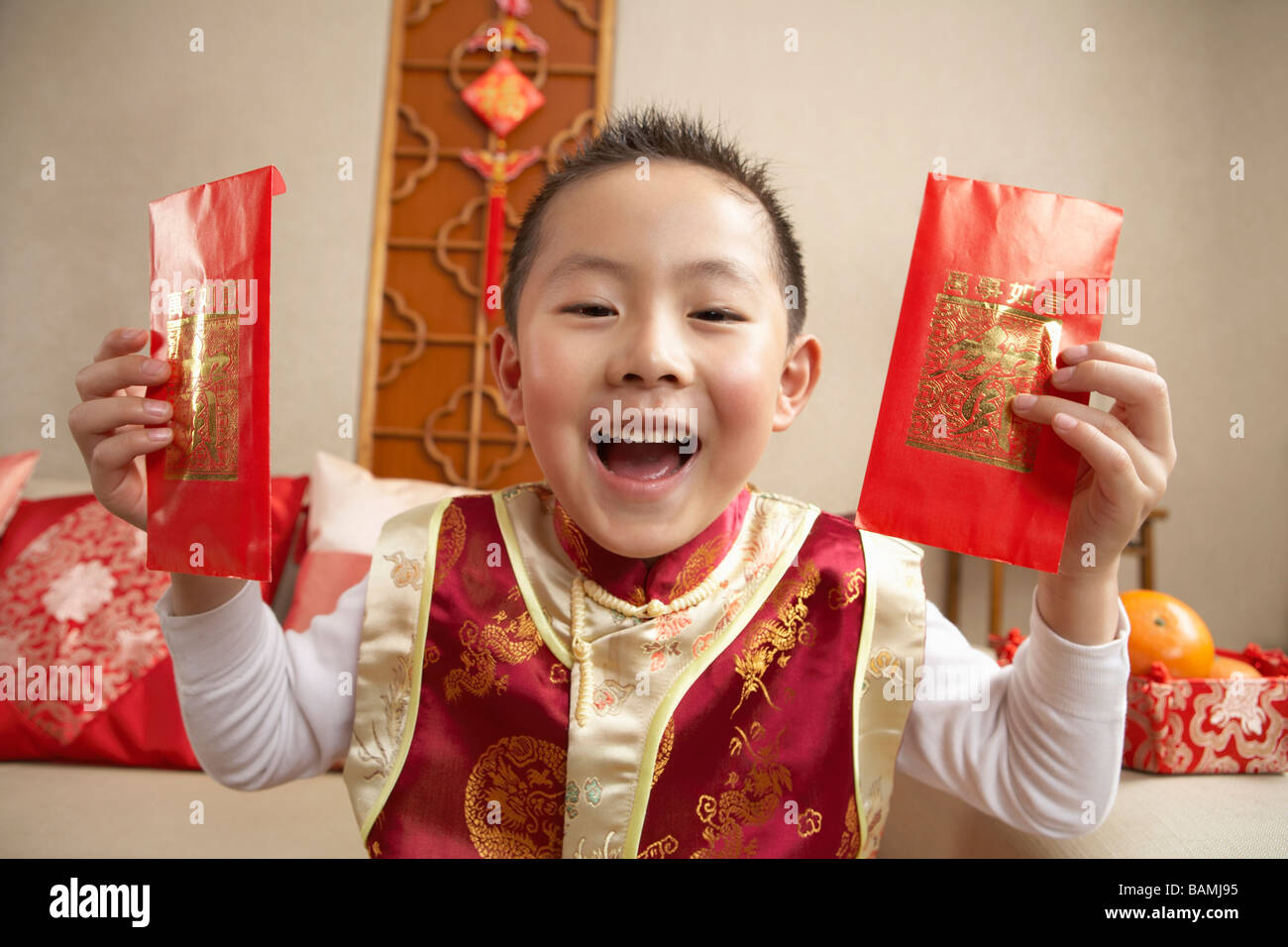 Young Boy In Traditional Clothing Holding Up Presents And Looking Happy - Stock Image