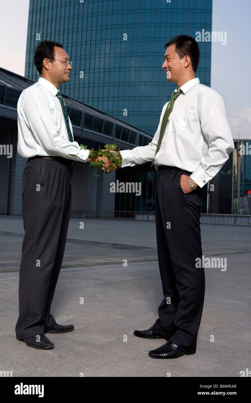 Two Businessmen Shaking Hands Wrapped In Ivy - Stock Image