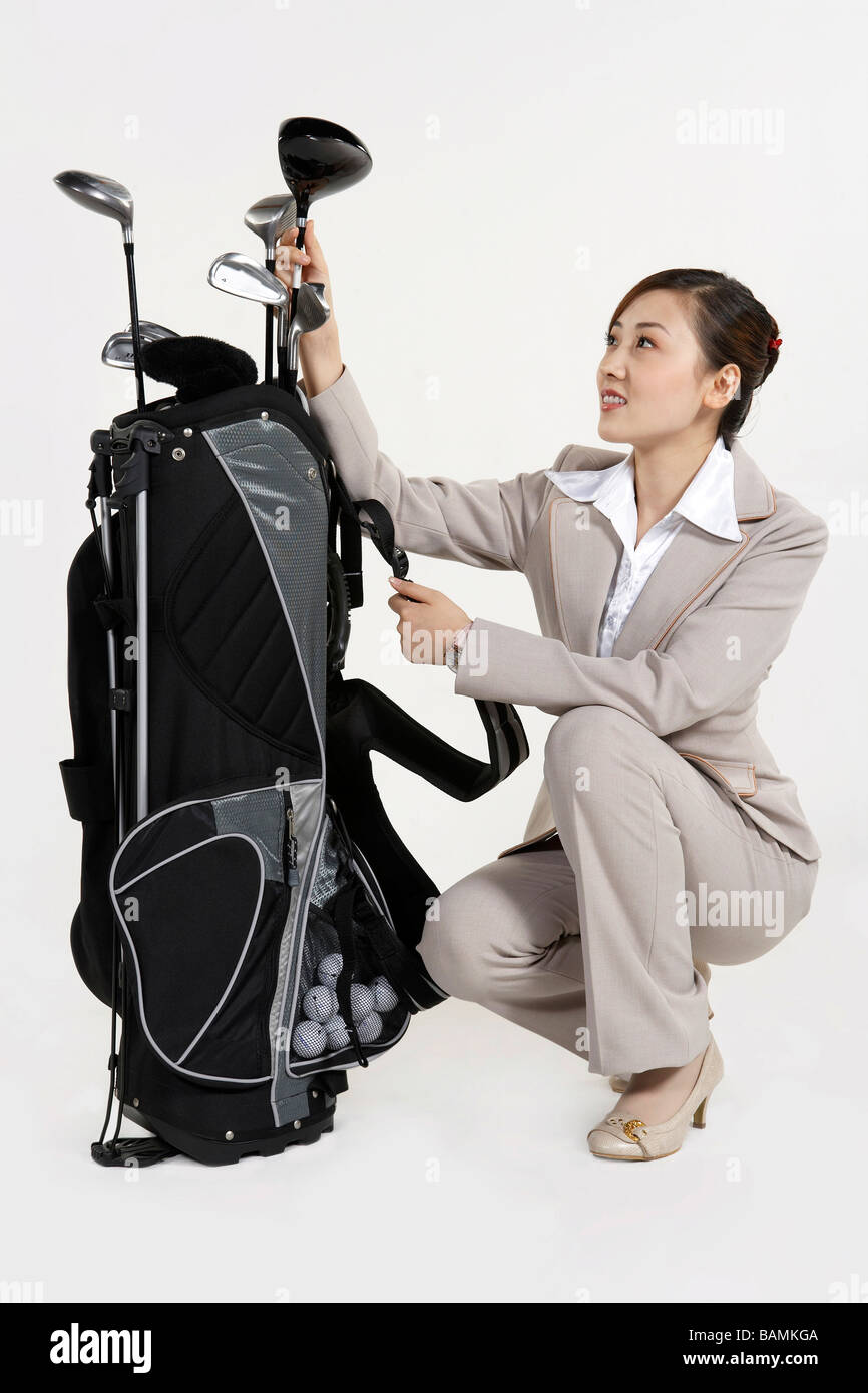 Businesswoman Kneeling To Choose A Golf Club - Stock Image