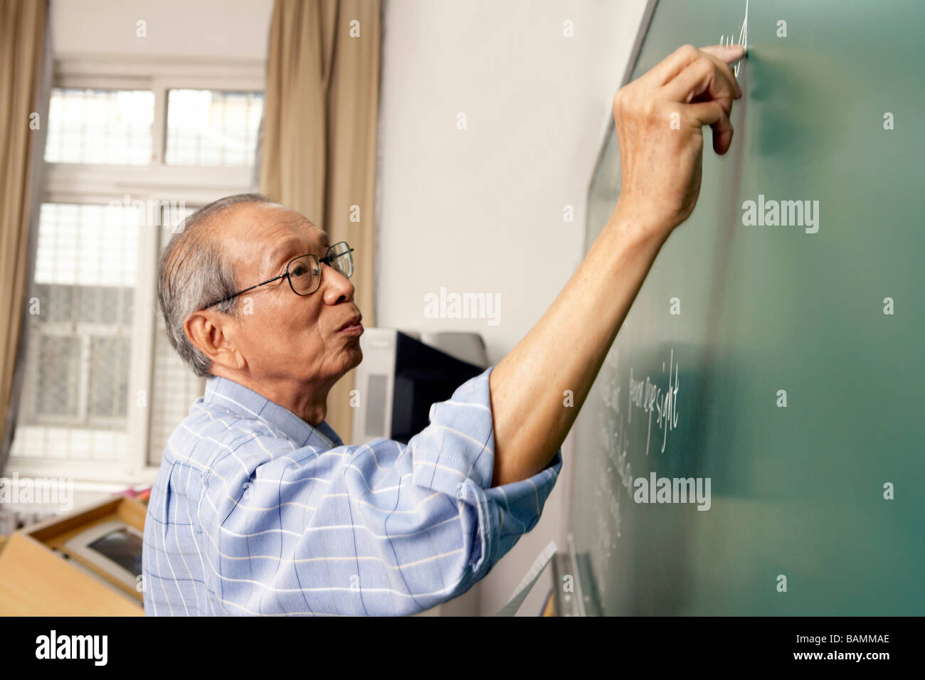 Teacher Writing On Blackboard - Stock Image