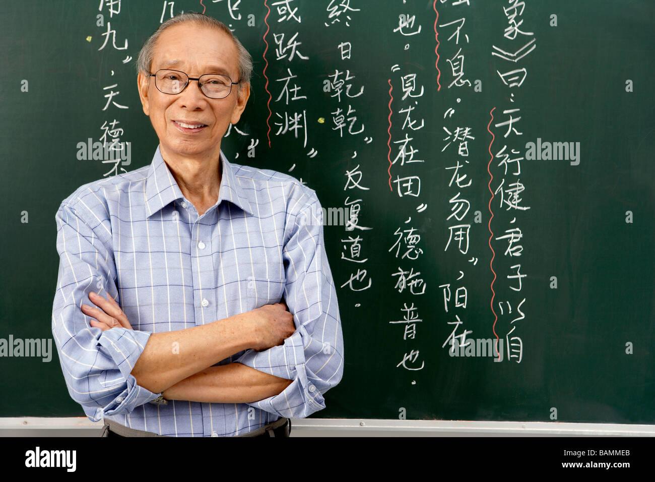 Teacher Standing By Blackboard, Arms Folded - Stock Image