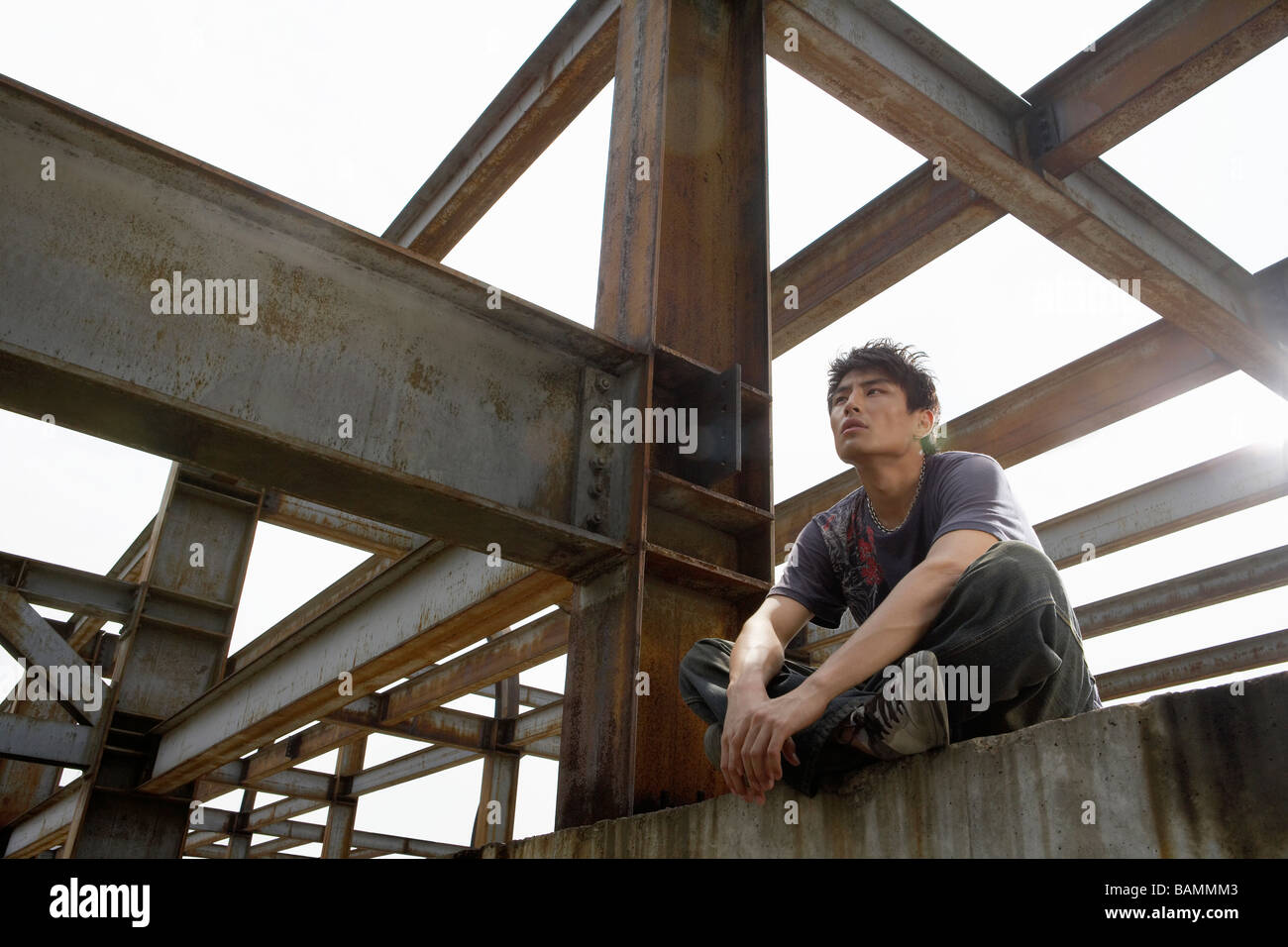 Young Man Sitting On A Beam In A Construction Site Stock
