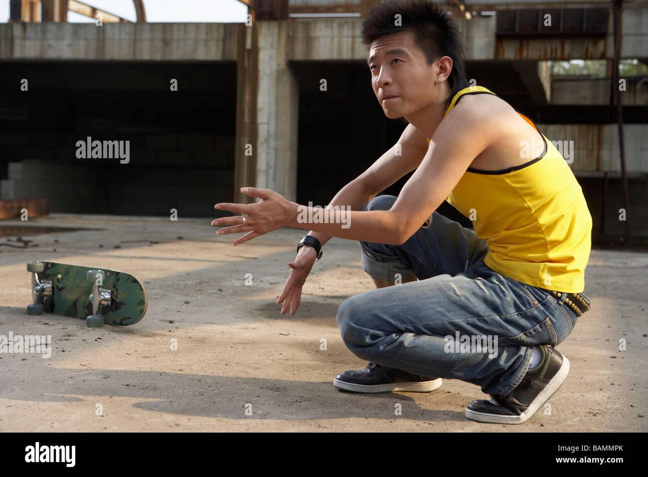 Man Crouching Down - Stock Image