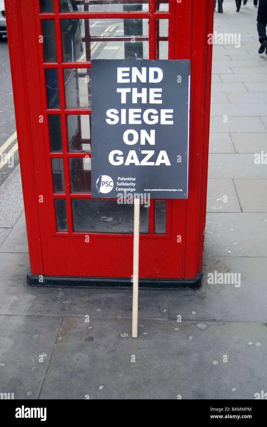 Siege in Gaza placard Red telephone kiosk London - Stock Image