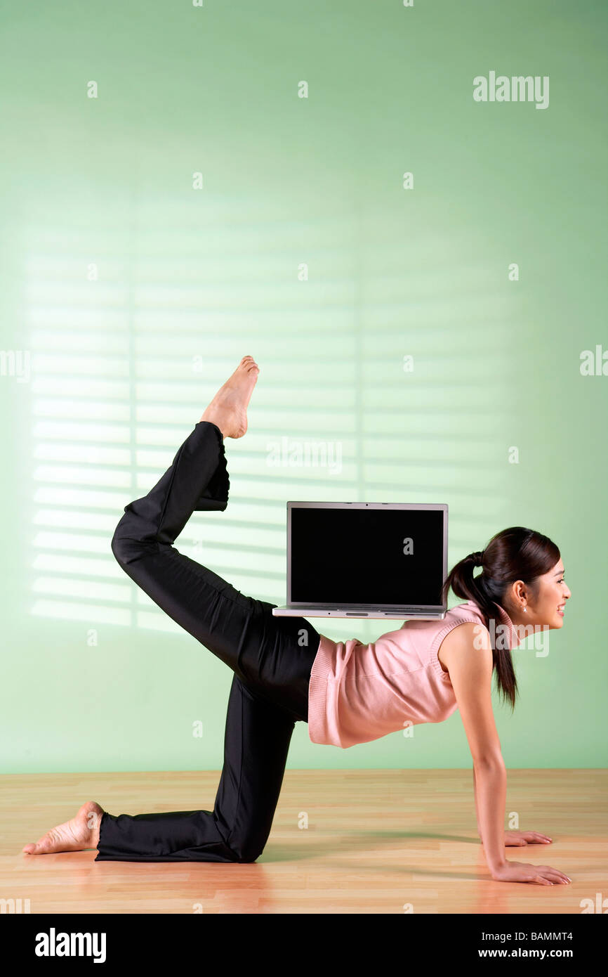 Woman Balancing Laptop Computer On Her Back - Stock Image