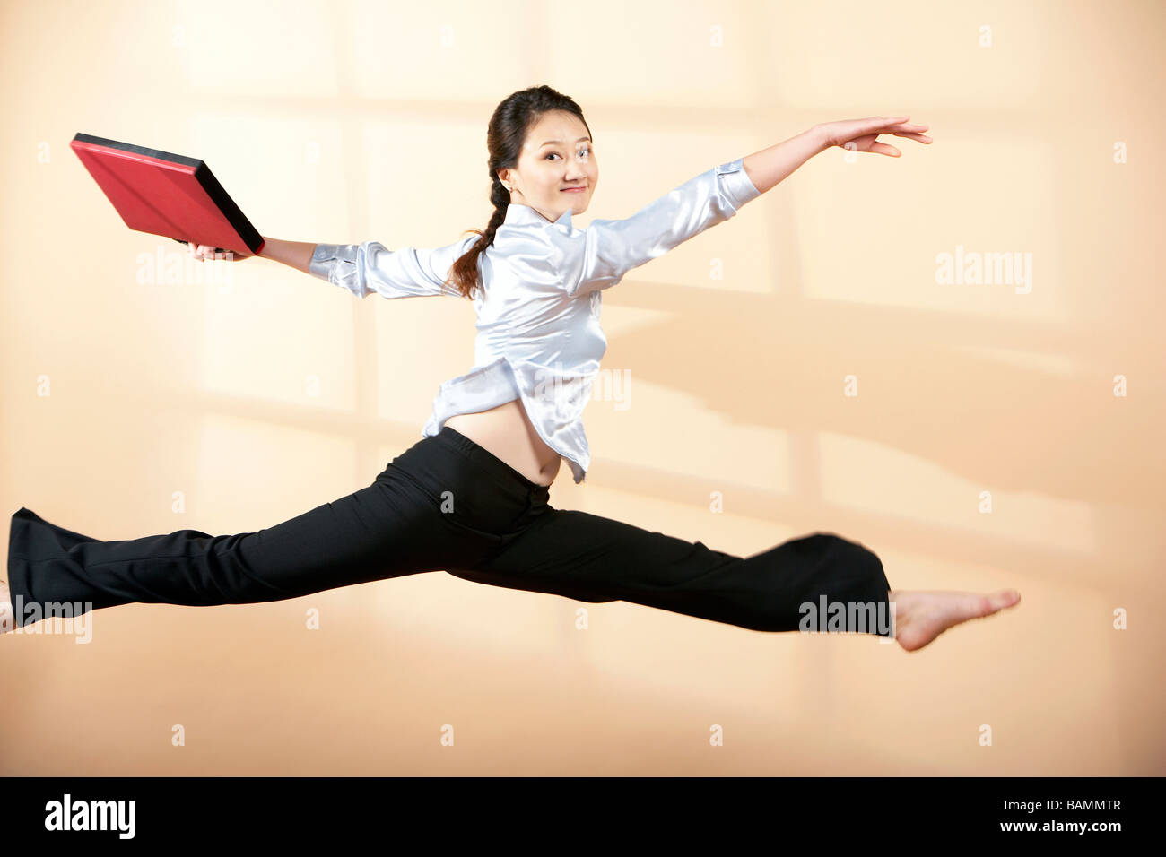 Woman Leaping Through The Air - Stock Image