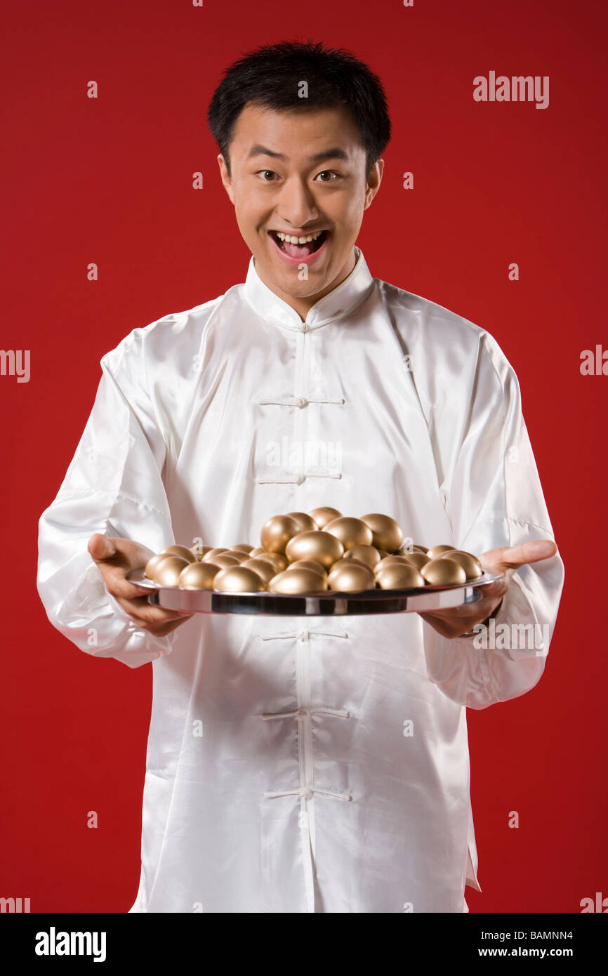 Man With Tray Of Golden Eggs - Stock Image