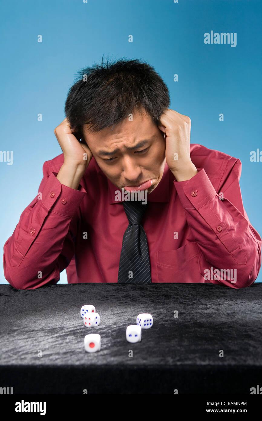 Businessman Looking At Dice In Despair - Stock Image