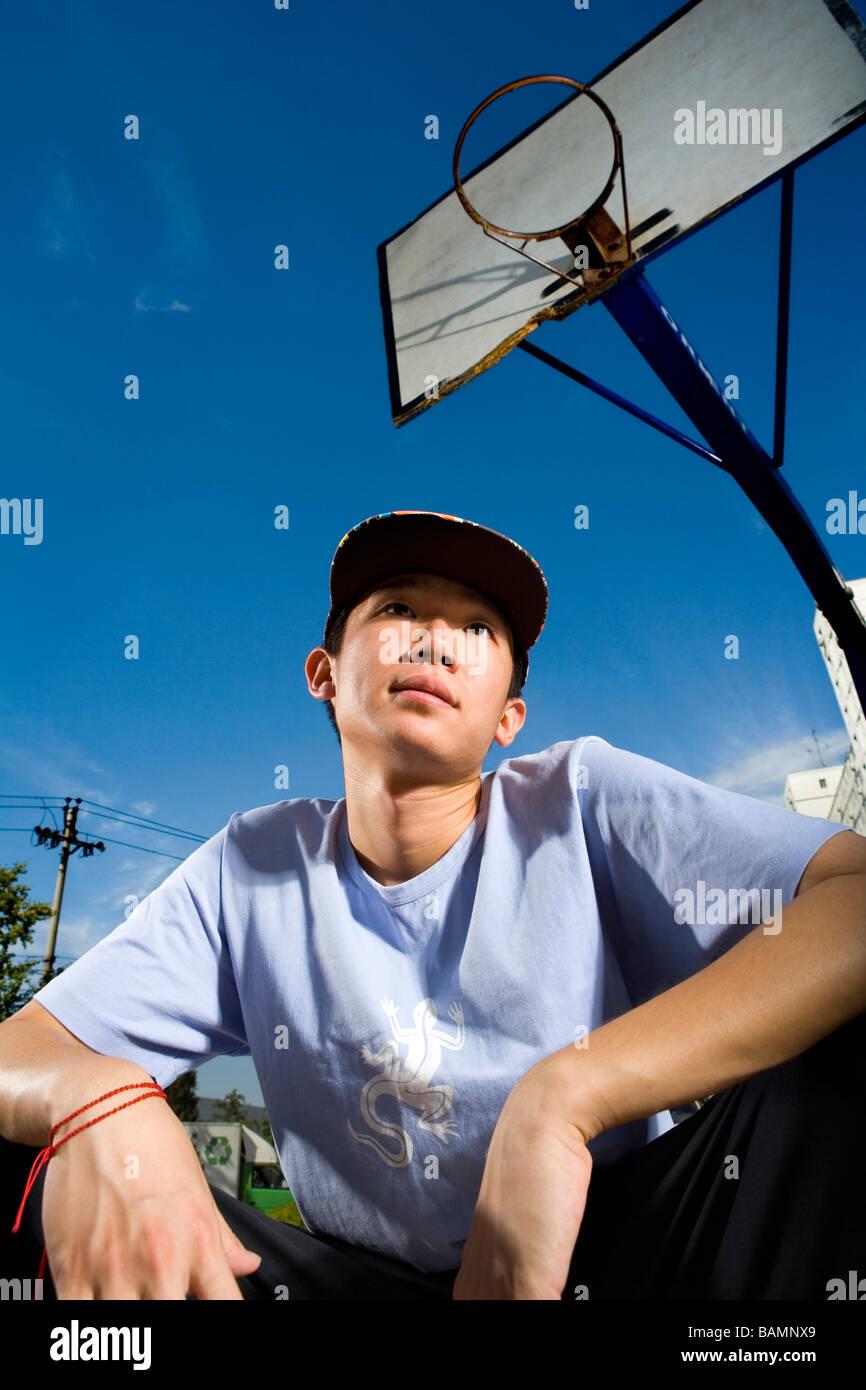 Teenage Boy Crouching On Basketball Court - Stock Image
