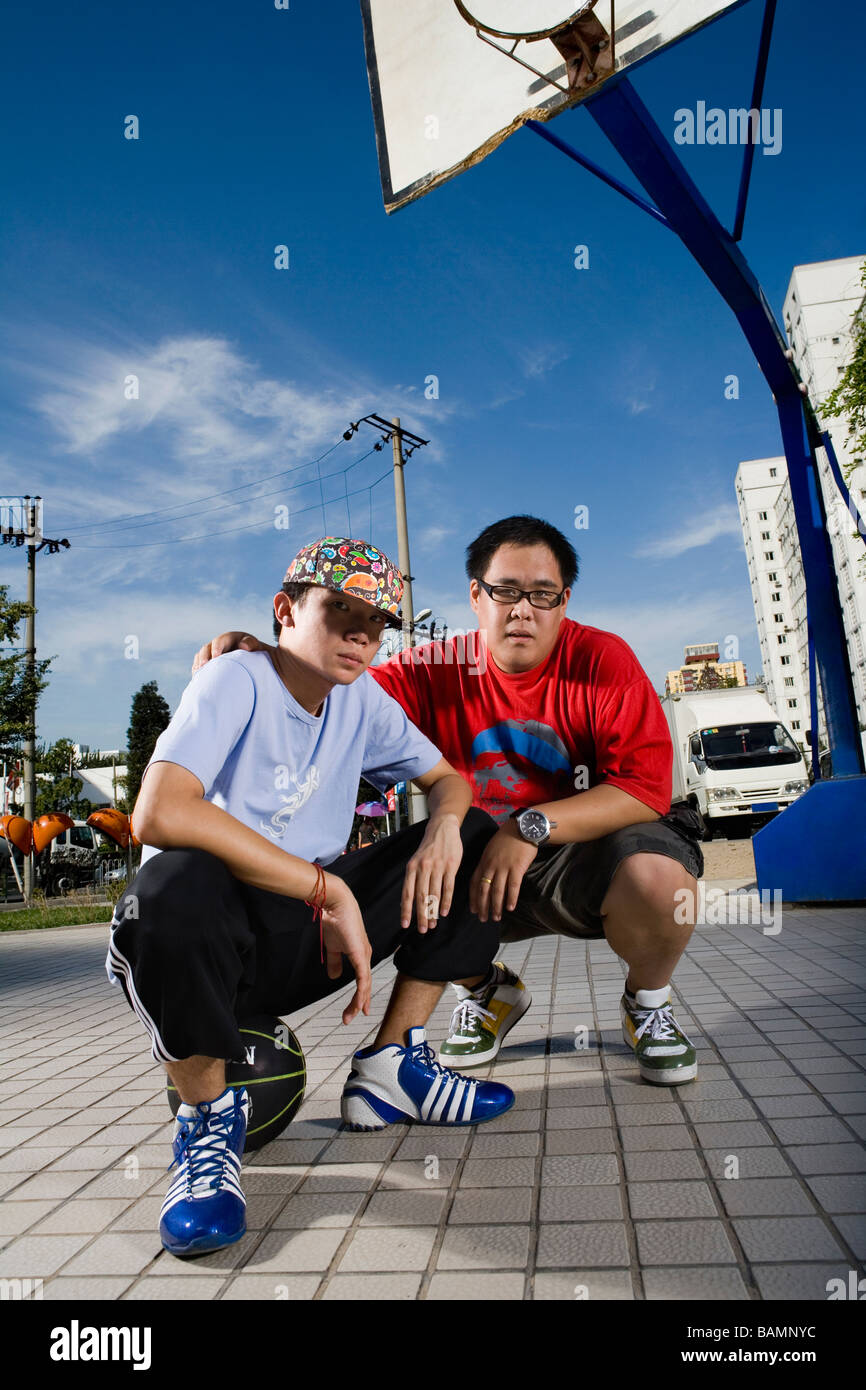 Two Boys Hanging Out On A Basketball Court - Stock Image