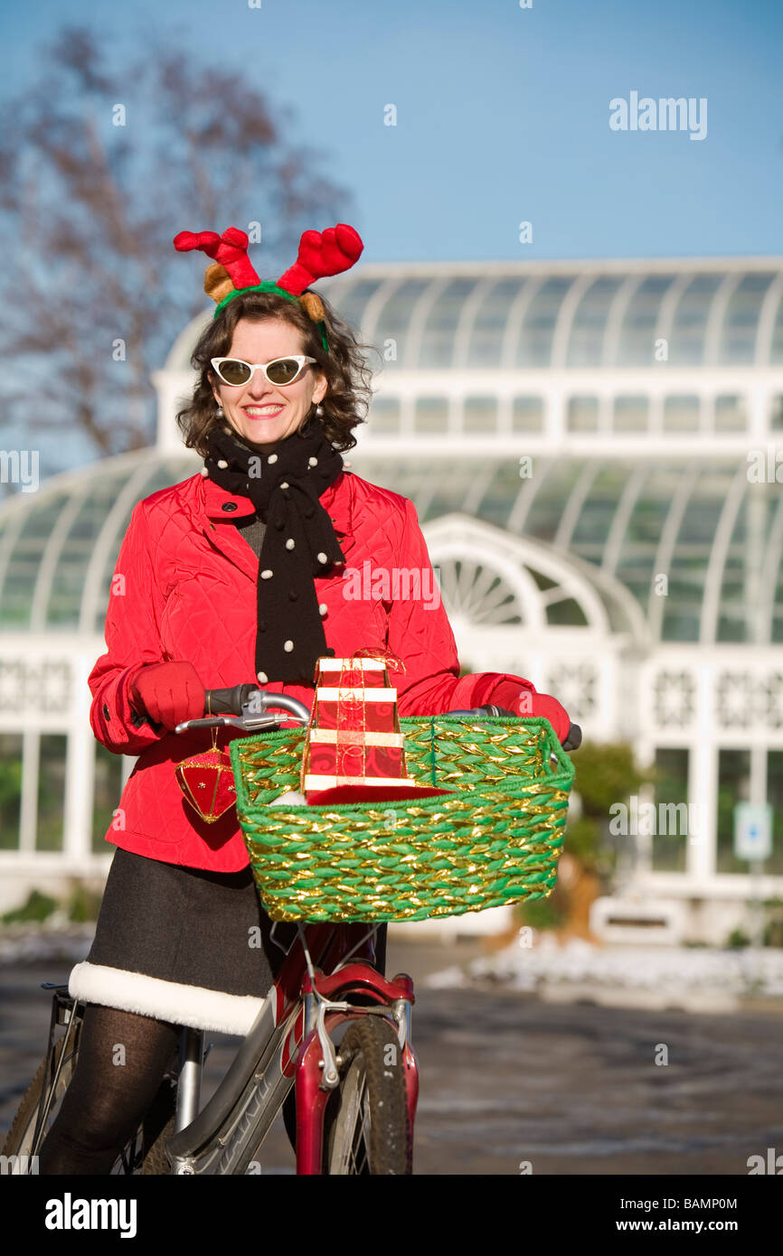 Woman in Christmas attire on a bicycle ride Stock Photo