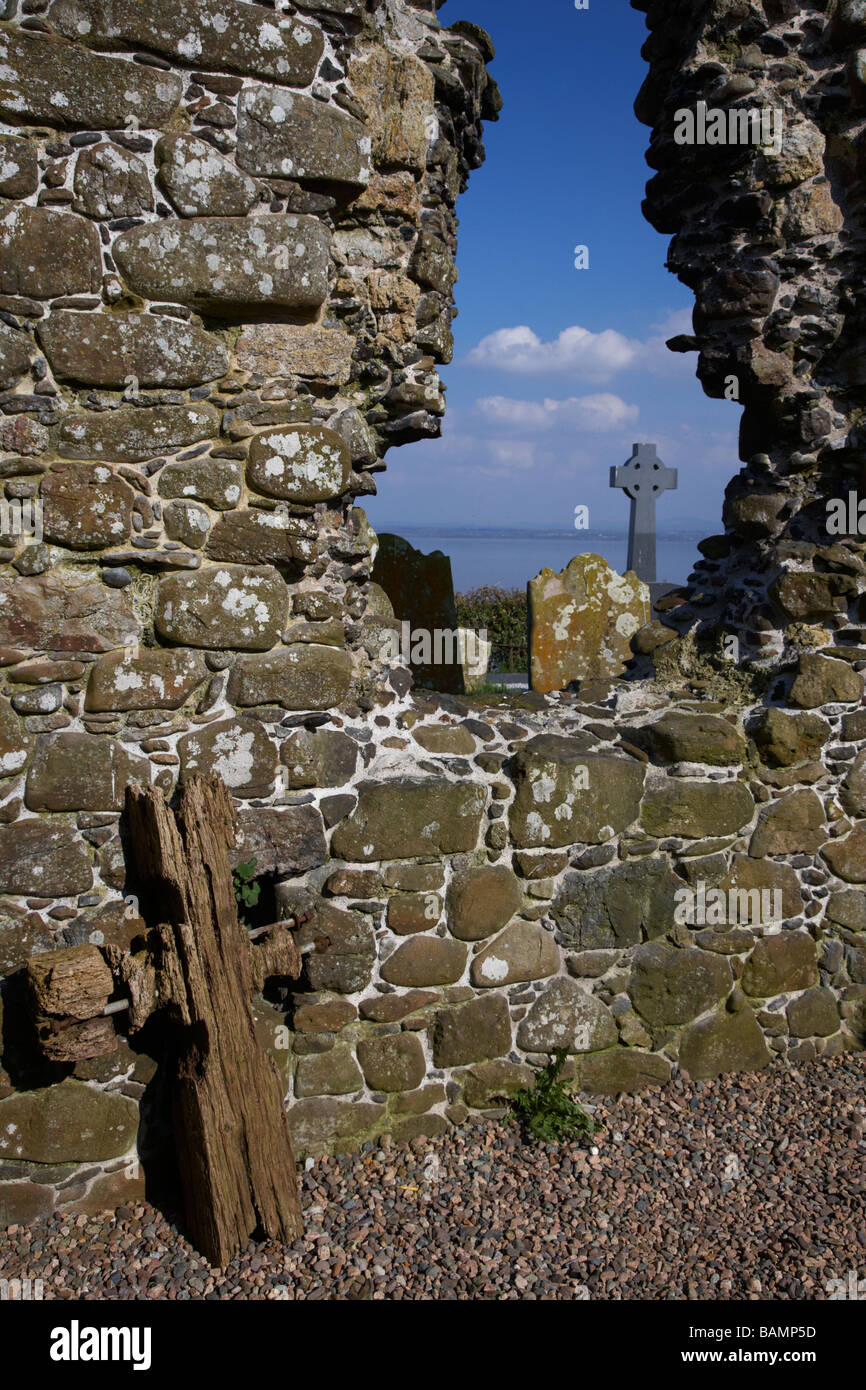 looking out through hole in the gable wall of 13th century cranfield church and graveyard on the shores of lough - Stock Image