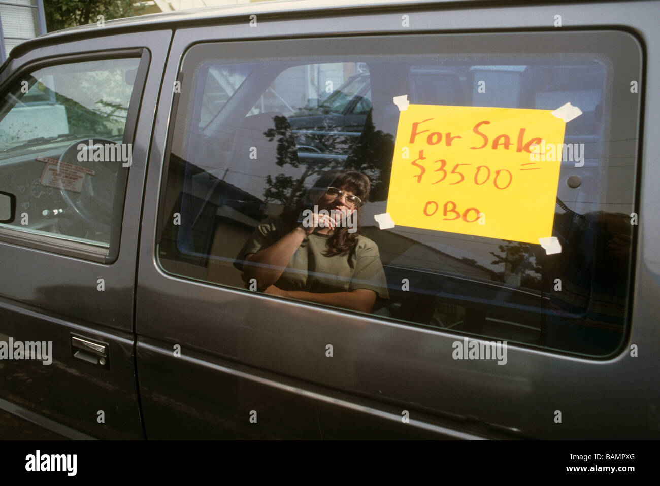 Woman reflect window car sale for sign post price examine buy sell ...