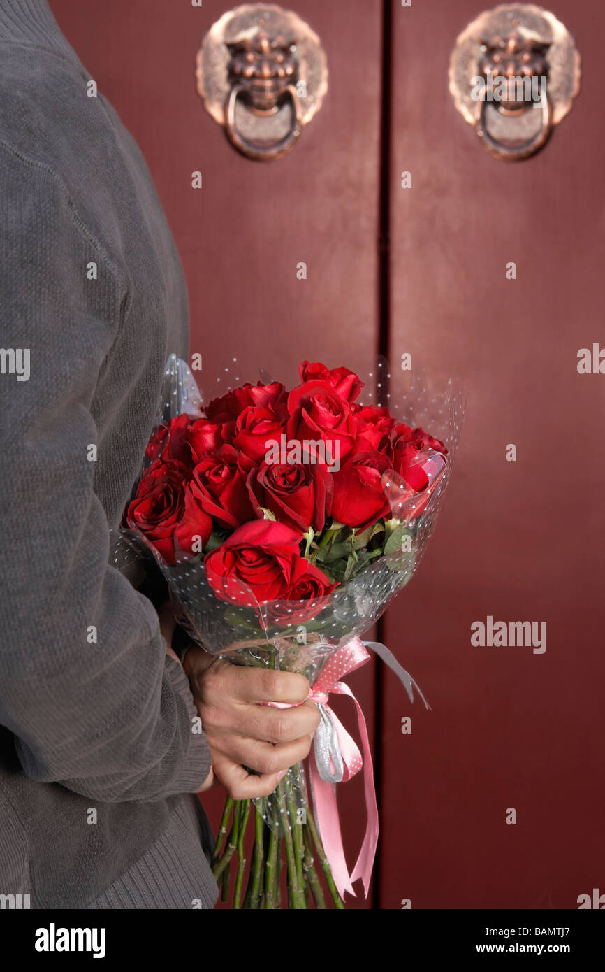 Young Man Waiting At Front Door With A Bunch Of Roses Behind His Back - Stock Image