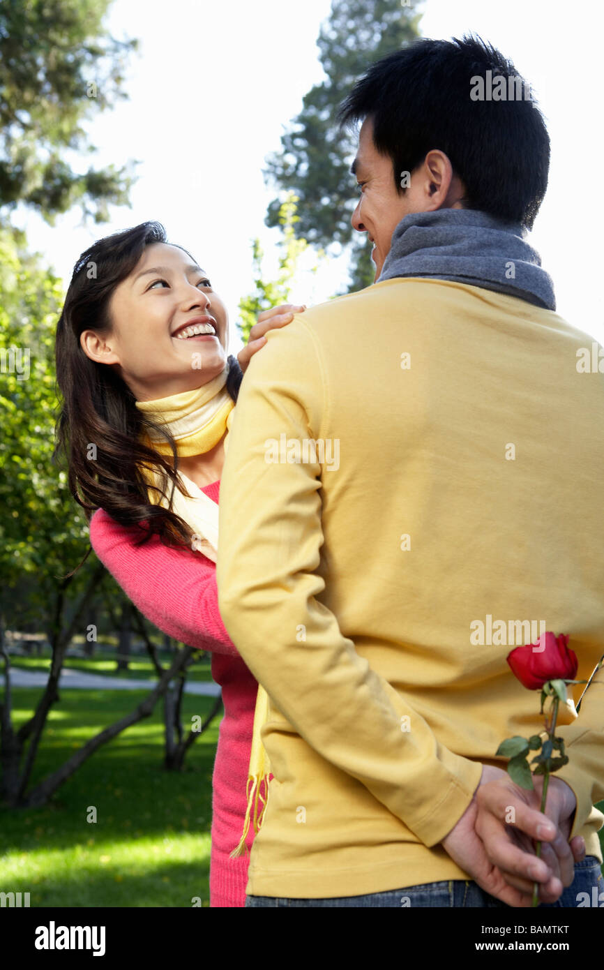 Young Man Surprising Girlfriend With Red Rose - Stock Image