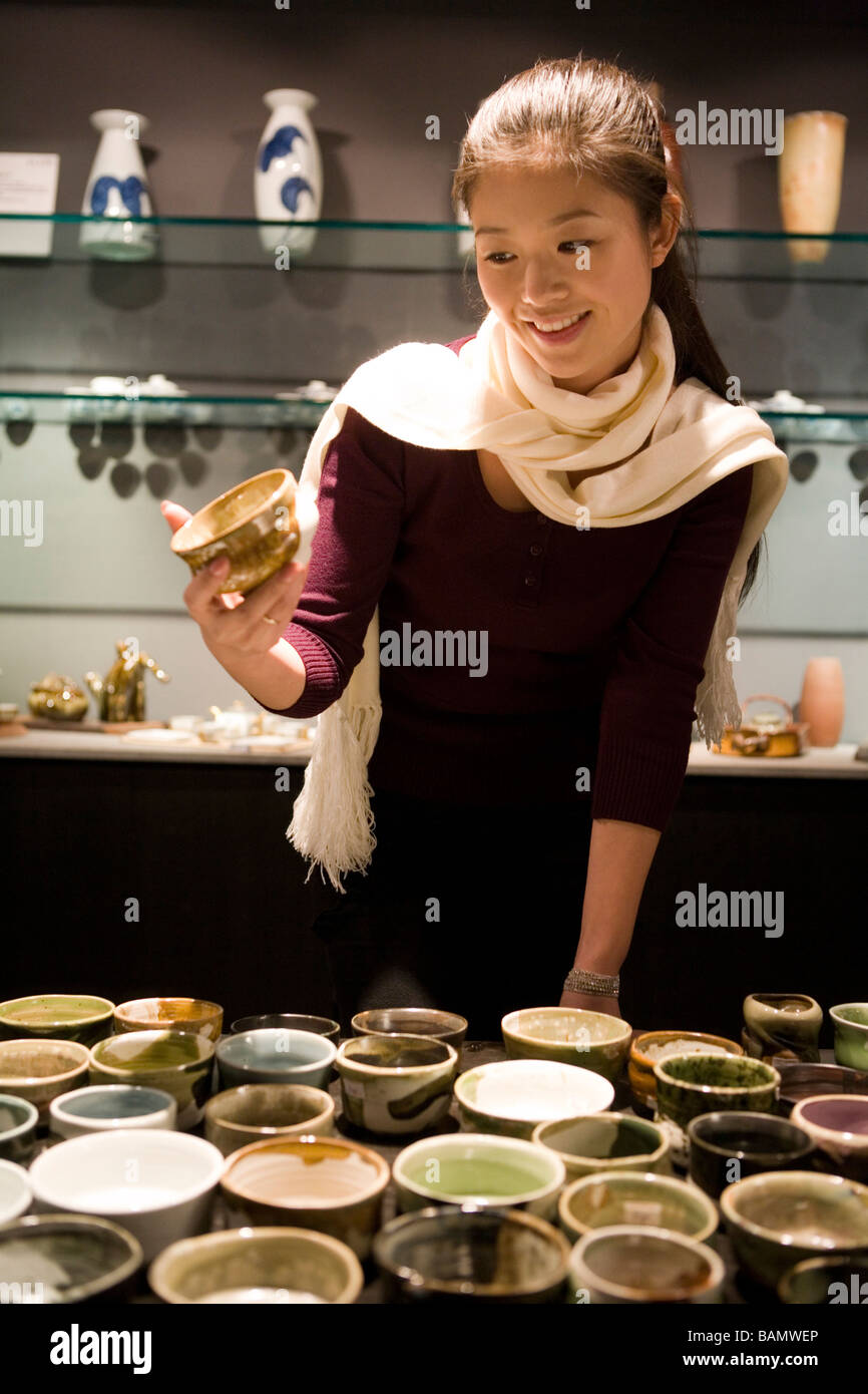 Young Woman Looking At Objects In Shop - Stock Image