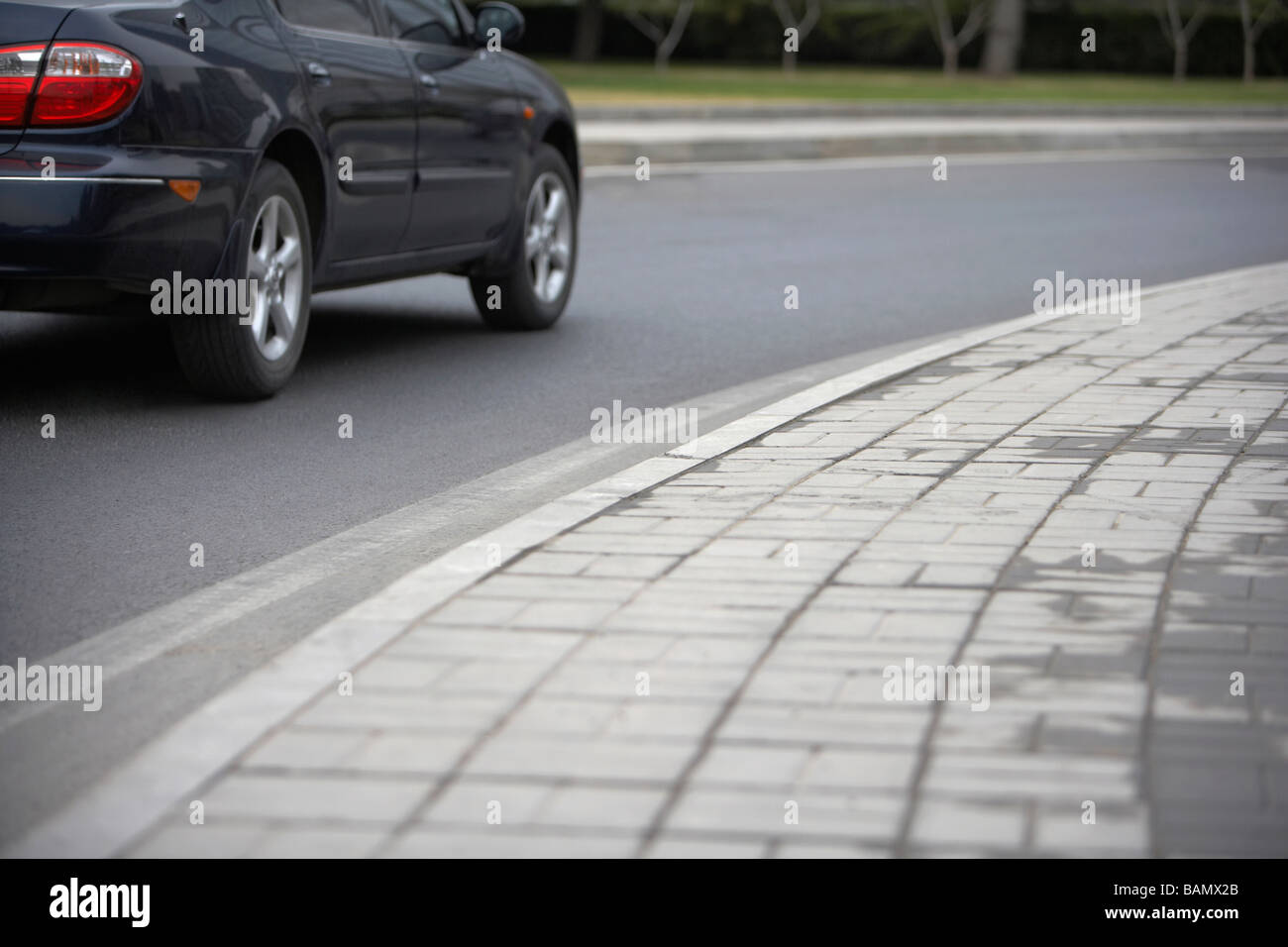 Low Angle View Of  A Concrete Block Pavement  With A Car Driving Past Stock Photo