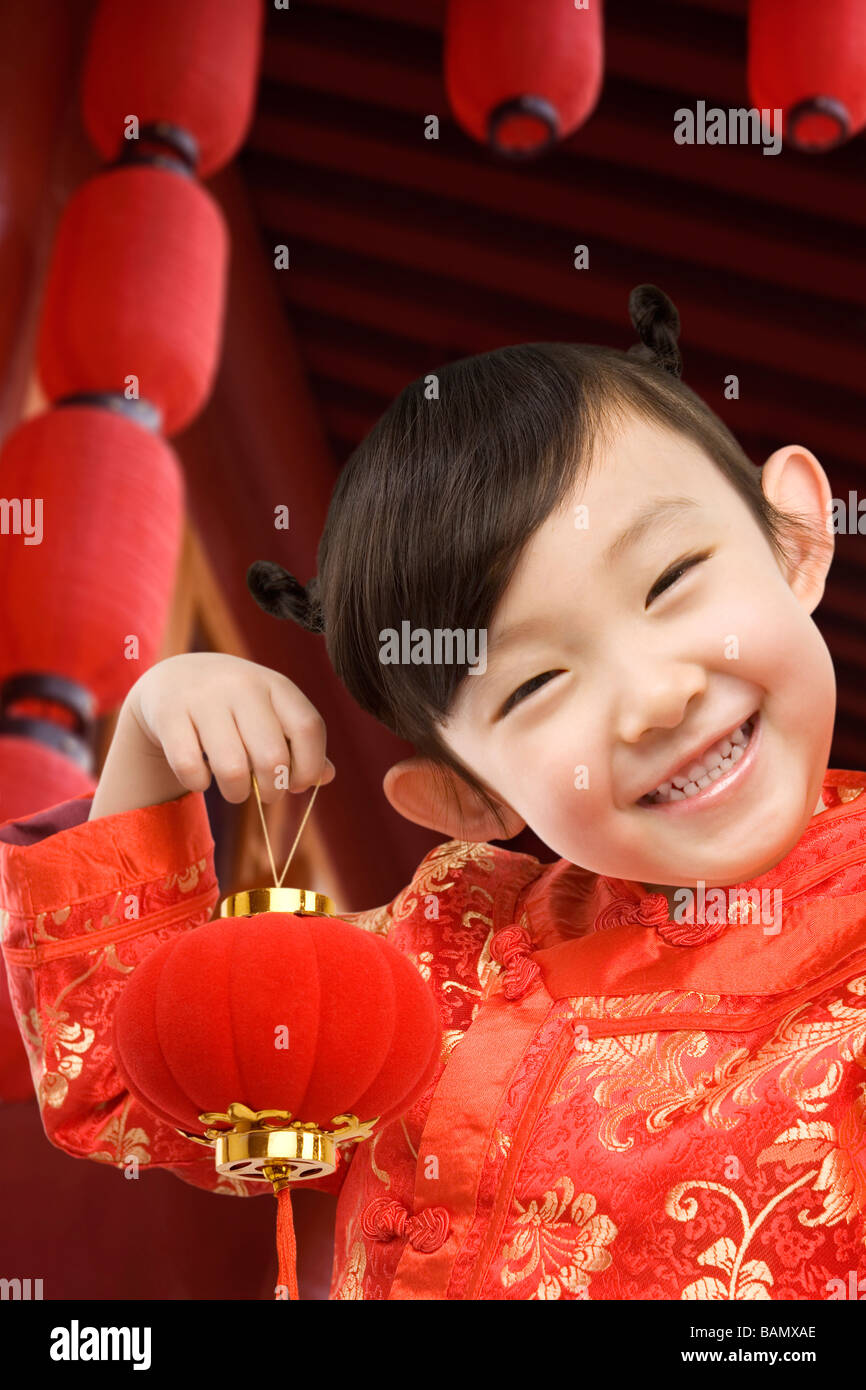 Young girl in festival Chinese New Year clothing, smiling at camera, holding Chinese lantern - Stock Image