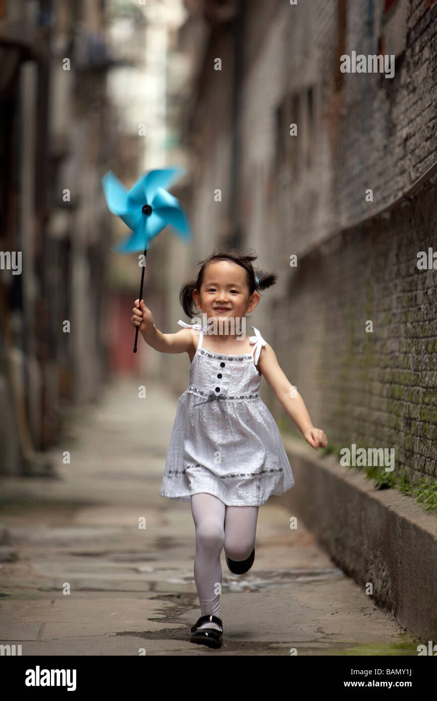 A child runs with a paper pinwheel - Stock Image