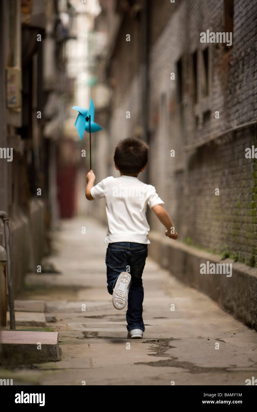 A child runs with a paper pinwheel Stock Photo