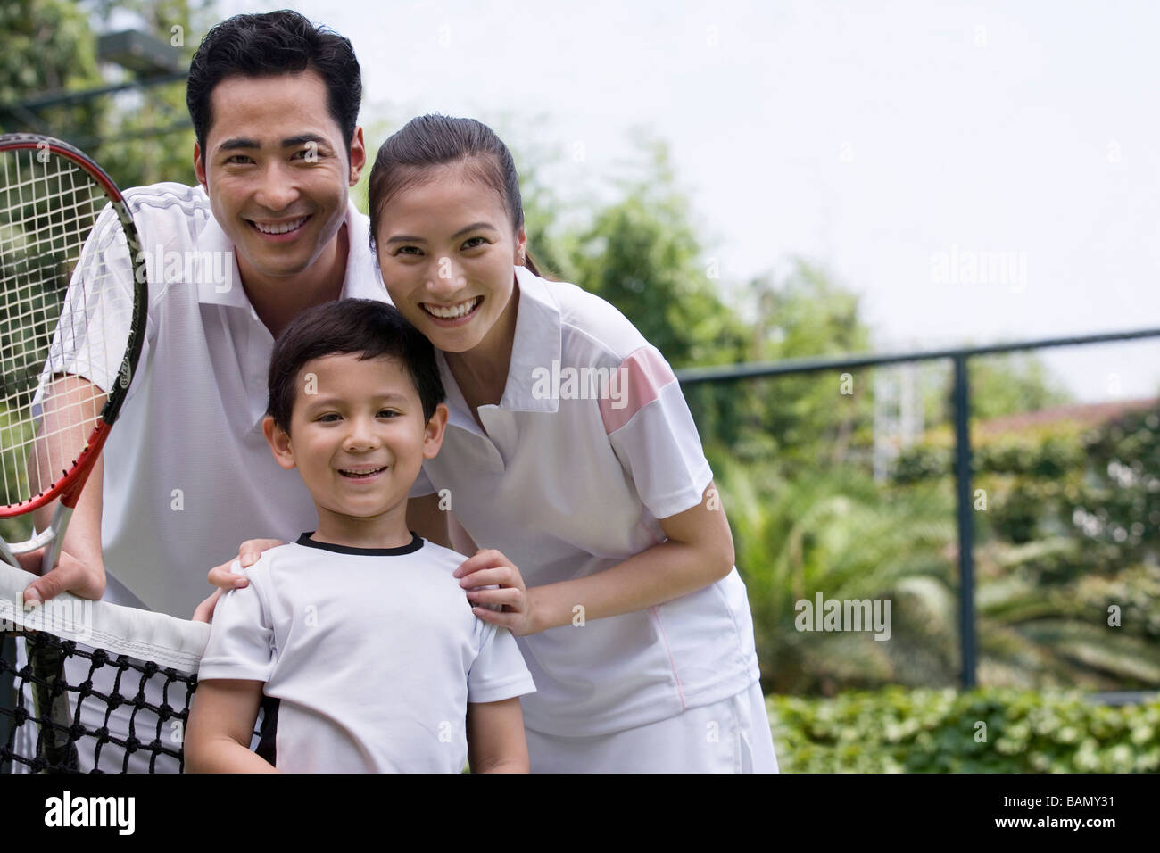 Portrait of a one child family on the tennis court - Stock Image