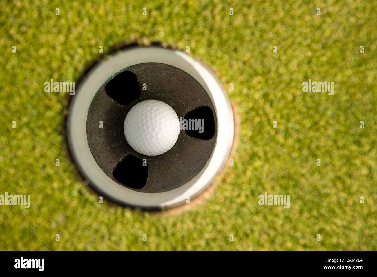 Golf ball in hole - Stock Image