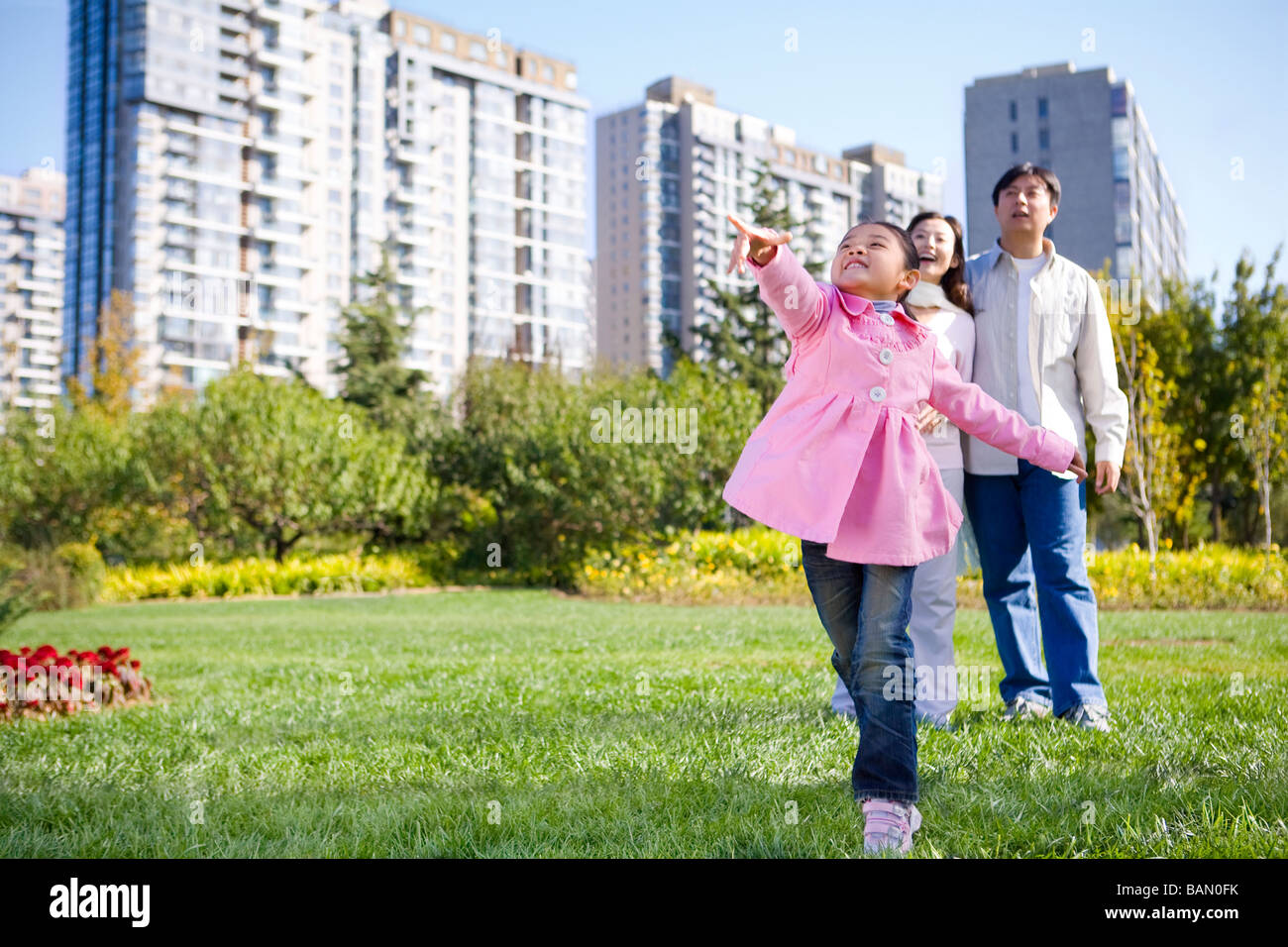 A young girl throws a paper airplane, while her parents look on - Stock Image