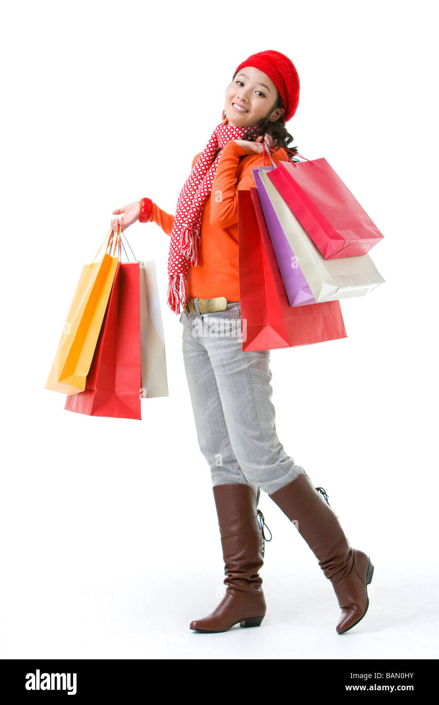 Young woman holding up shopping bags - Stock Image