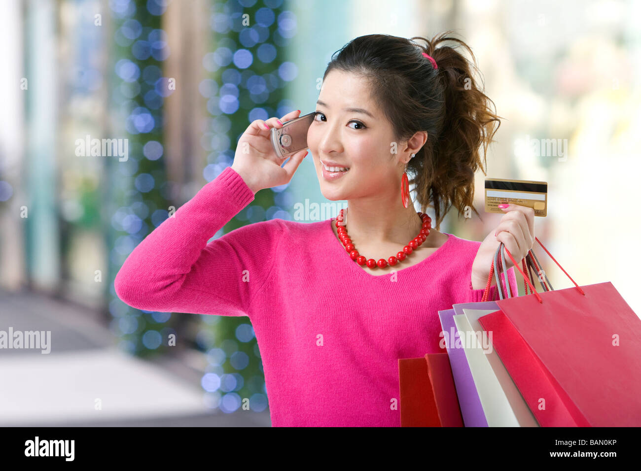 Young woman holding up her mobile phone and credit card out shopping - Stock Image