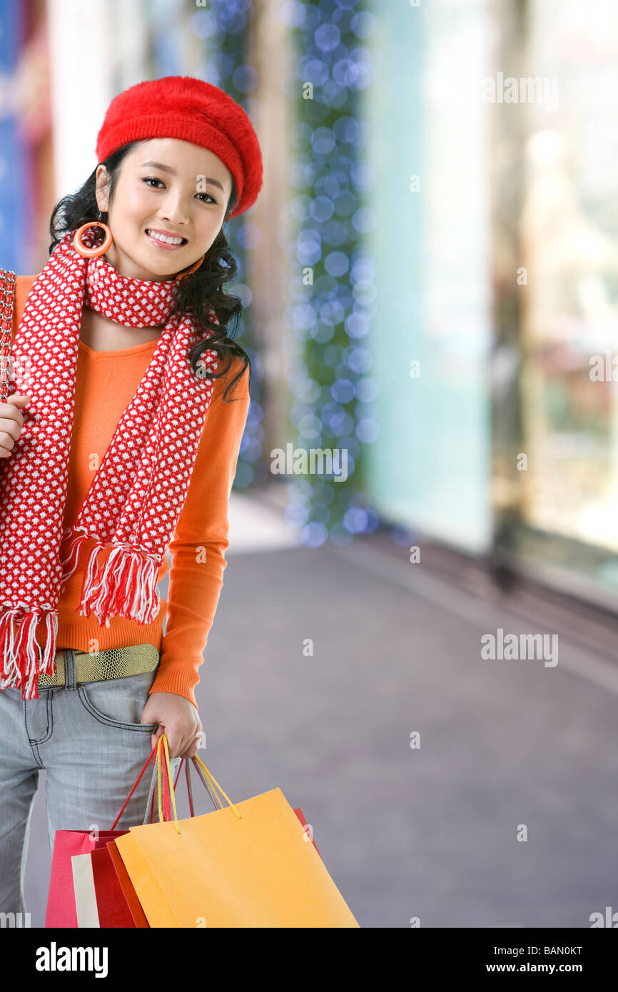 Young woman with shopping bags, at a retail center - Stock Image