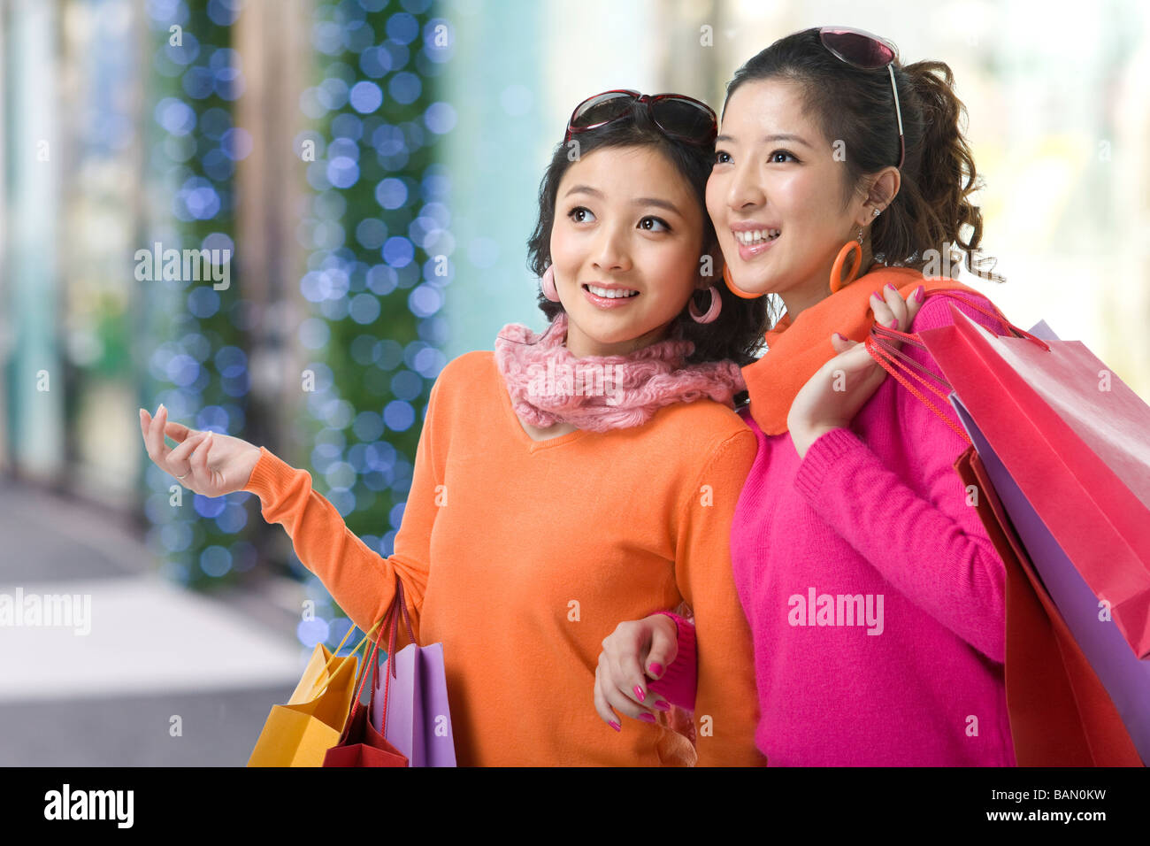Two young women holding up shopping bags - Stock Image